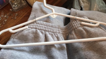 Hang pants with two safety pins on a regular hanger